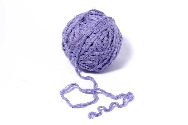 Purpurowa woolen piłka odizolowywająca na bielu nić