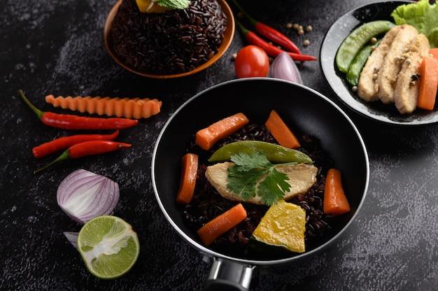 Purpurowe jagody ryżu gotowane z grillowaną piersią kurczaka. liście dyni, marchewki i mięty w patelni.