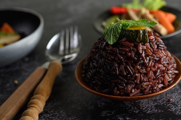 Purpurowe jagody ryżu gotowane z grillowaną piersią kurczaka liście dyni z marchwi liście mięty w naczyniu i łyżka, widelec, czyste jedzenie.
