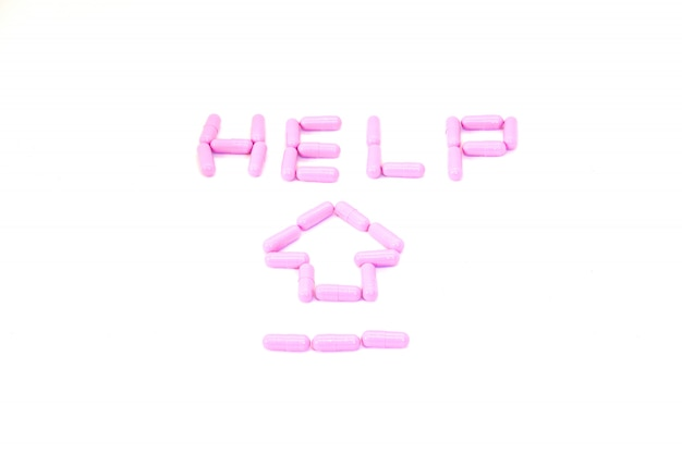 Purpurowe kapsuły aranged w tekście 'pomoc' i strzała w opiece zdrowotnej dla pojęcia pomocy
