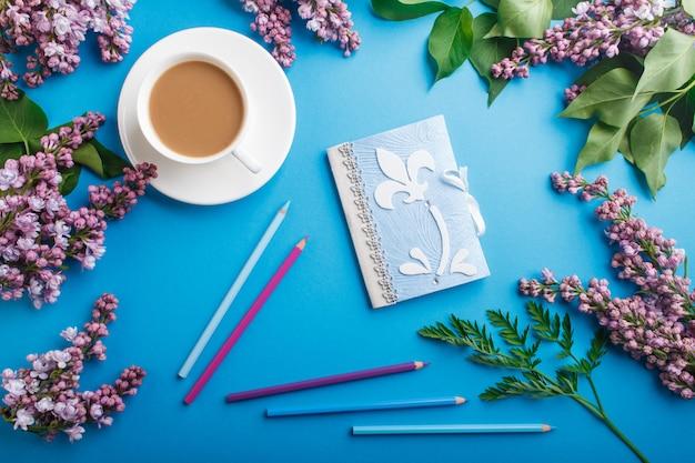 Purpurowe kwiaty bzu i filiżanka kawy z notebookiem i kredkami na pastelowym niebieskim tle.