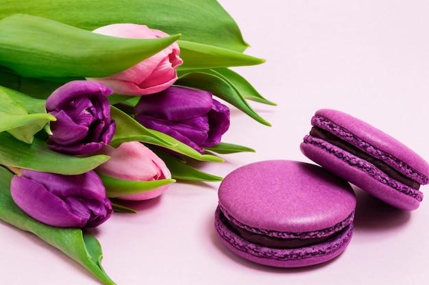 Purpurowe makaroniki, bukiet fioletowych i różowych tulipanów na jasnoróżowym tle