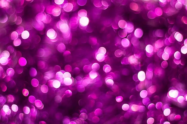 Purpurowego błyszczącego błyskotliwości plamy bokeh wakacyjny piękny abstrakcjonistyczny tło