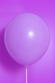 Purpurowy balon na purpurowym tle z cieniem. blask boczny.