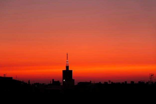 Purpurowy czerwony lato wschód słońca, widok z góry starej wieży kościoła nad miastem.