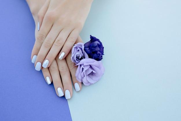 Purpurowy manicure na prostym tle z kwiatem