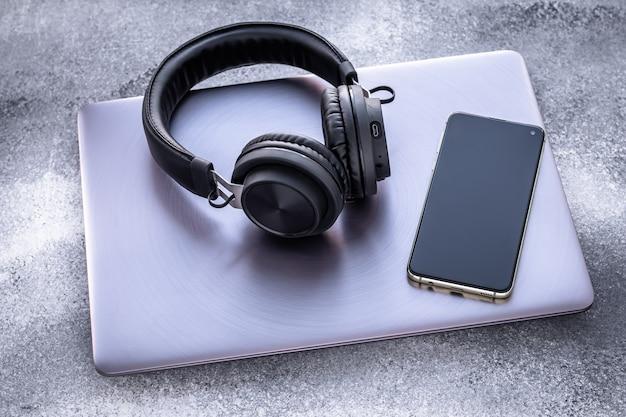Purpurowy metalowy laptop, czarne przenośne słuchawki i telefon komórkowy na szarym tle grunge. izolacja społeczna, styl życia.