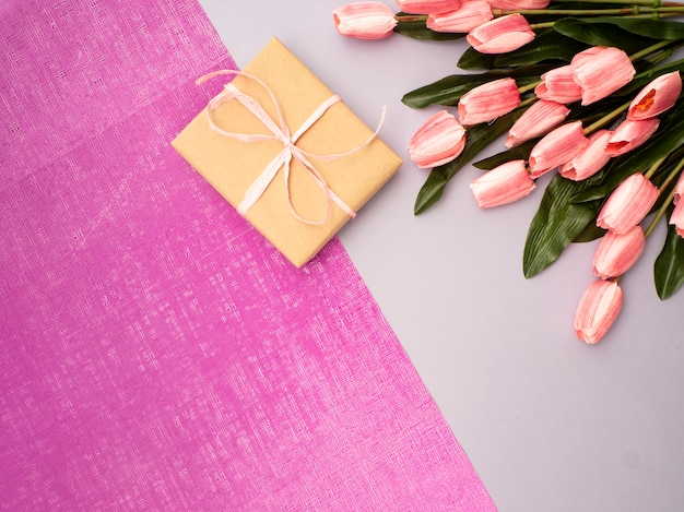 Purpurowy tulipan i prezenta pudełko na purpurowym tle