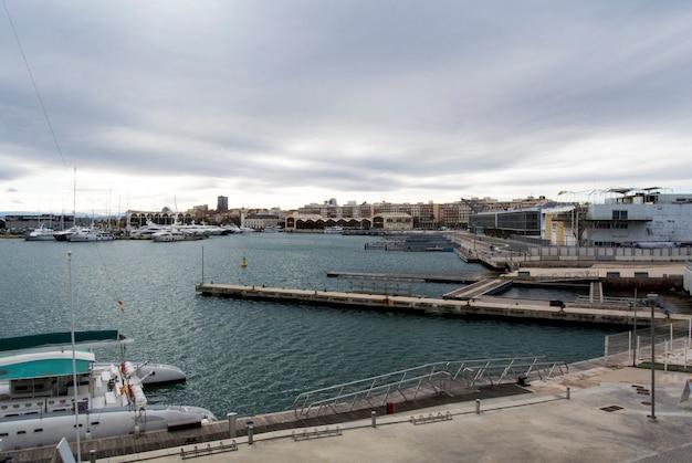 Puści doki w walencja porcie, hiszpania. port walencji na morzu śródziemnym. refleksja w wodzie. puste doki w hiszpańskim porcie w walencji na początku wiosny. pochmurne niebo.