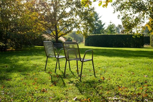 Puści metali krzesła wśród świeżej zieleni w parku