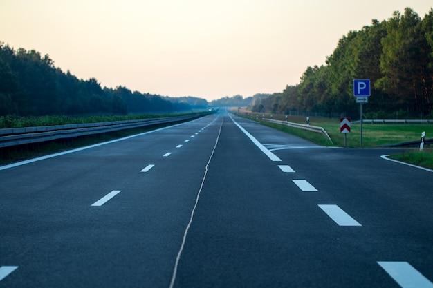 Pusta asfaltowa droga, pole i błękitne niebo z chmurami.