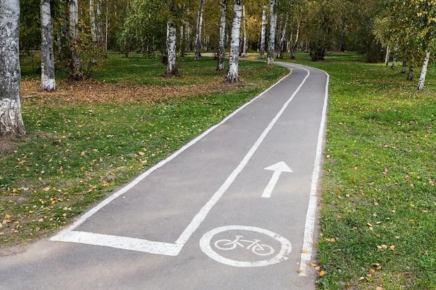 Pusta asfaltowa ścieżka rowerowa z ikoną i strzałką w miejskim parku zamienia się w las