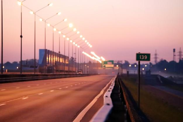Pusta autostrada ciągnąca się w dal o wschodzie słońca