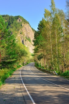 Pusta autostrada wśród brzóz i górskich klifów chakasja syberia rosja