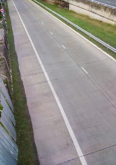 Pusta betonowa droga do wjazdu do systemu drogi ekspresowej z metalowym ogrodzeniem dla bezpieczeństwa na przedmieściach, widok z przodu z miejscem na kopię.
