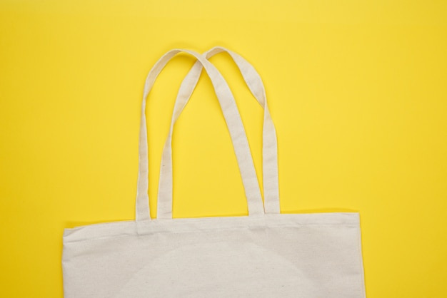 Pusta beżowa torba tekstylna na żółtej powierzchni