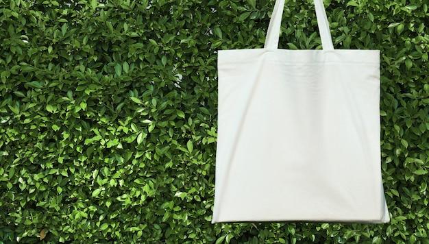 Pusta biała bawełniana torba na zielonym leavs tle. koncepcja przyjazna dla środowiska