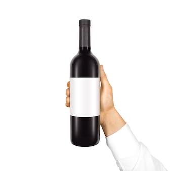 Pusta biała etykieta makiety na czarnej butelce czerwonego wina w ręku na białym tle