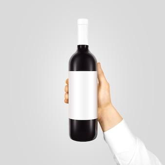 Pusta biała etykieta makiety na czarnej butelce czerwonego wina w ręku