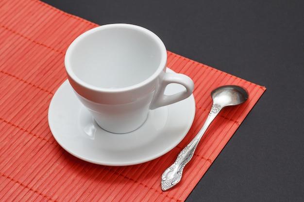 Pusta biała filiżanka kawy, spodek i łyżka na czerwonej bambusowej serwetce z czarnym tłem. widok z góry.