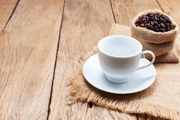 Pusta biała filiżanka kawy z ziaren kawy na podłodze drewnianej deski