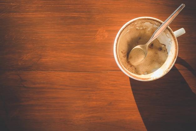 Pusta biała filiżanka po napoju na drewnianym stole z kopii przestrzenią dla teksta lub projekta