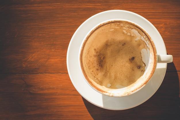 Pusta biała filiżanka z latte pianą po pić na drewnianym stole z kopii przestrzenią dla teksta lub projekta