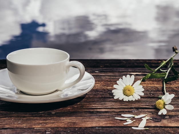 Pusta biała filiżanka z wiosna kwiatami