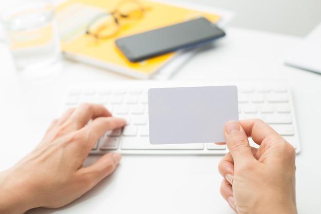 Pusta biała karta kredytowa w dłoni na klawiaturze.