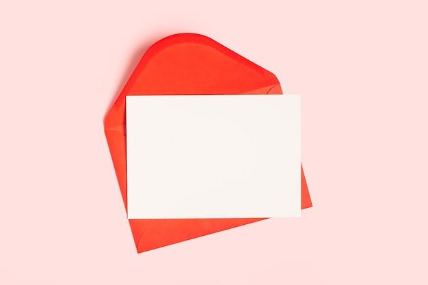 Pusta biała karta z makiety szablonu czerwonej koperty papierowej