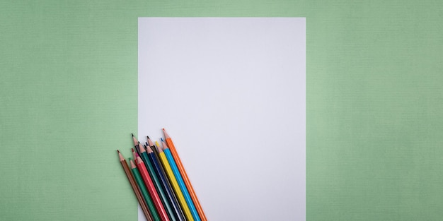 Pusta biała kartka i kolorowe kredki do rysowania na gładkim teksturowanym tle z przestrzenią