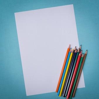 Pusta biała kartka i kolorowe kredki do rysowania na zwykłym teksturowanym tle z miejscem na kopiowanie i pisanie. układ, makieta wolna przestrzeń.