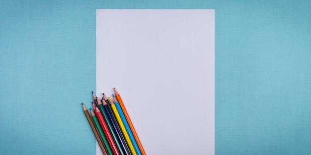 Pusta biała kartka i kolorowe kredki do rysowania na zwykłym teksturowanym tle