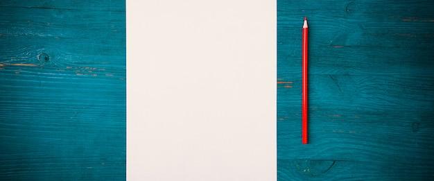Pusta biała kartka i ołówek do rysowania na drewnianym tle z miejscem do kopiowania