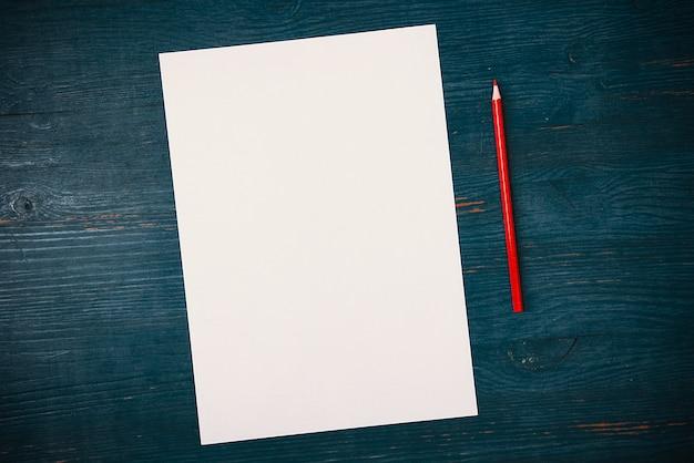 Pusta biała kartka i ołówek do rysowania na drewnianym tle z miejscem na kopiowanie i pisanie. układ, makieta wolna przestrzeń.