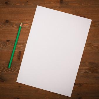 Pusta biała kartka i ołówek do rysowania na drewnianym tle
