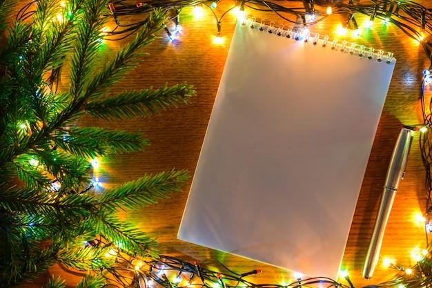 Pusta biała kartka notebooka z metalową patelnią na tle nowego roku.