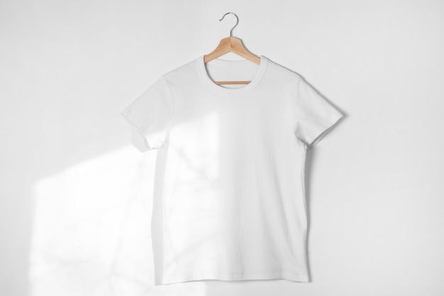 Pusta biała koszulka na białej ścianie