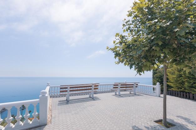 Pusta biała ławka na tle pejzażu morskiego. jasne tło, kopia przestrzeń