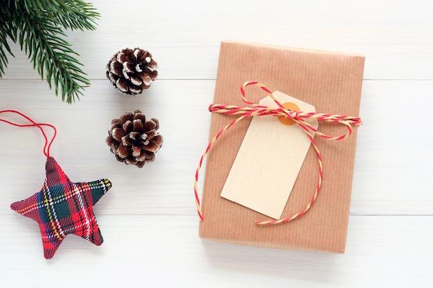 Pusta biała papierowa karta na brown rocznika prezenta pudełku na białym drewnianym tle