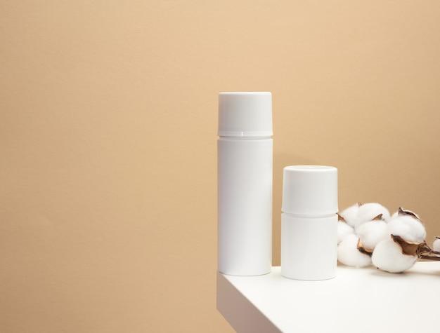 Pusta biała plastikowa butelka na beżowym tle. produkty kosmetyczne do znakowania żelu, kremu, balsamu, szamponu. makiety kosmetyków ekologicznych