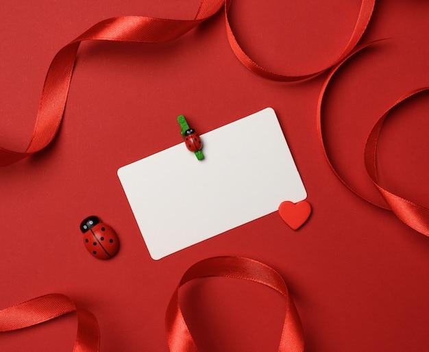 Pusta biała prostokątna wizytówka na czerwonym tle, wystrój czerwoną jedwabną wstążką