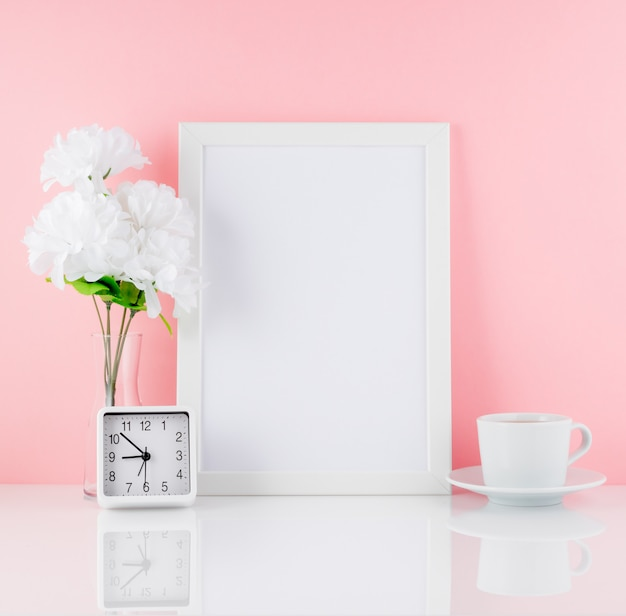 Pusta biała ramka, kwiat, zegar, filiżanka kawy lub herbata na białym stole na tle różowej kopii ściany. .