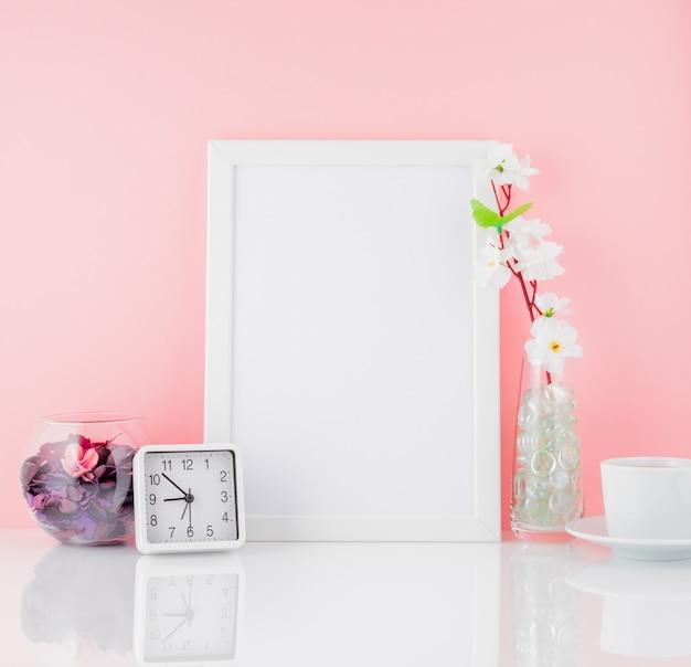 Pusta biała ramka, kwiat, zegar i filiżanka kawy lub herbaty na whi