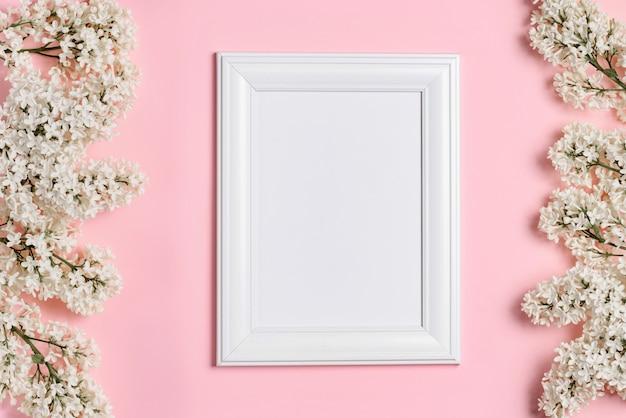 Pusta biała ramka na zdjęcia i białe kwiaty bzu na różowej ścianie.