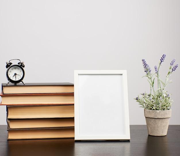 Pusta biała ramka na zdjęcia, stos książek i doniczka z rosnącą lawendą