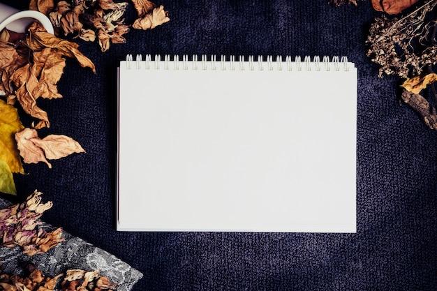 Pusta biała strona notatnika otoczona suchymi brązowymi żółtymi liśćmi i kwiatami na ciemnoniebieskim