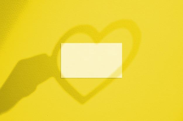 Pusta biała wizytówka z nakładką cienia dłoni i serca. makieta nowoczesnej i stylowej karty marki. rozświetlający kolor pantone roku 2021.