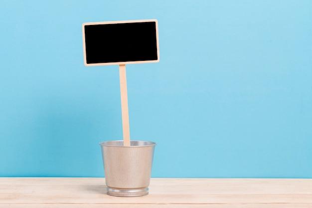 Pusta blackboard etykietka z żelaznym wiadrem odizolowywającym na błękitnym tle