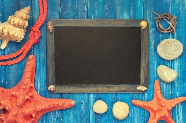 Pusta blackboard z dennymi skorupami, arkaną i gwiazdową ryba na błękitnym drewnie, kopii przestrzeń